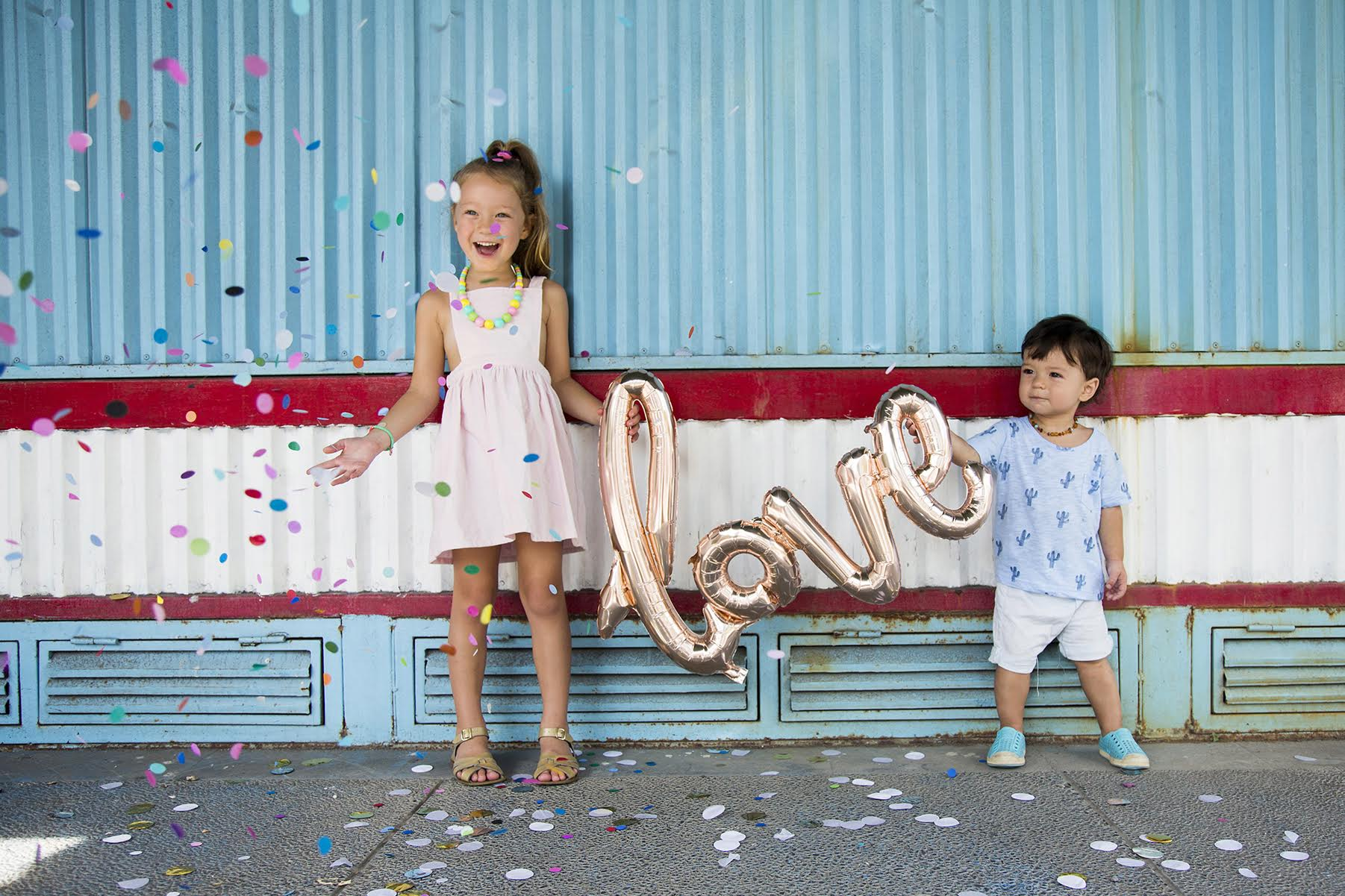 a boy and girl holding love balloon