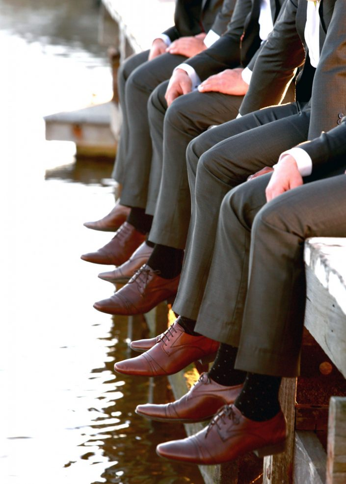 groomsmen sitting on dock