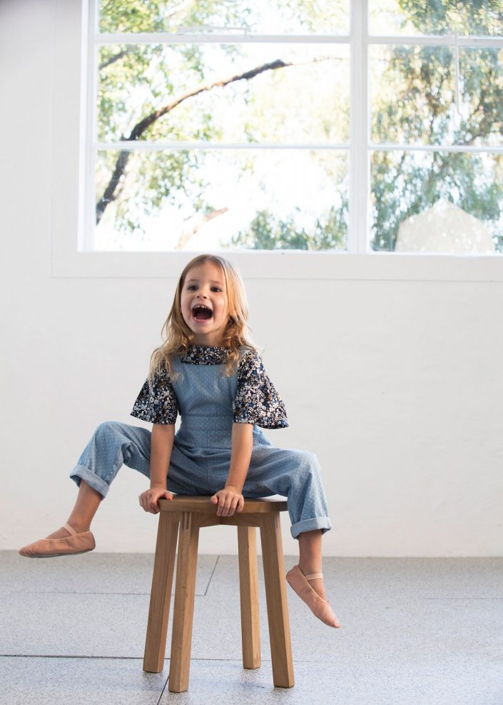 young girl on wooden stool wearing denim overalls